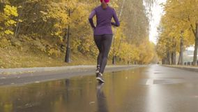 Young sportswoman running along the road. Slow motion of young sportswoman running along the road. Dolly shot, rear view stock video