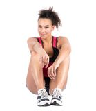 Young sportswoman sits on the floor Stock Images