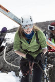 Young sportswoman ski mountaineer climbing on rope on rock Royalty Free Stock Photography