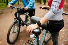 Chill on bicycles. Young sportswoman with smartwatch and bicycle and her boyfriend having short break during cycle chill royalty free stock photos