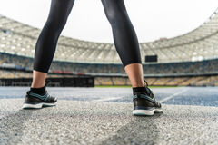 Young sportswoman in sneakers standing on running track stadium Royalty Free Stock Photos