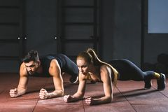 Young sportswoman and sportsman doing push ups stock photos