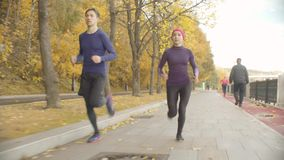 Young sportswoman and sportsman running along the road. Dolly shot of young sportswoman and sportsman running along the road stock footage
