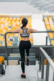 Young sportswoman in sportswear stretching at handrail on stadium. Back view of young sportswoman in sportswear stretching at handrail on stadium Stock Images