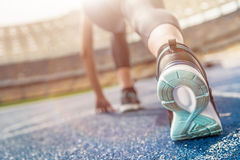 Young sportswoman in starting position on running track stadium Royalty Free Stock Image