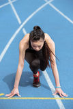 Young sportswoman in starting position on running track stadium Stock Photography