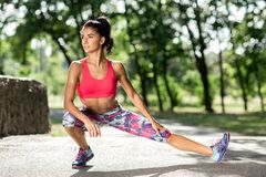 Young sportswoman stretching and preparing to run. Jogger or runner. Cardio. stock photography