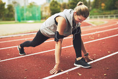 Young sportswoman stretching on track field Stock Photos