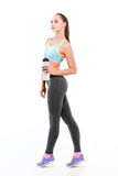 Young sportswoman on tiptoe with bottle of water Royalty Free Stock Images