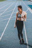 Young sportswoman with towel standing on running track stadium Royalty Free Stock Photos