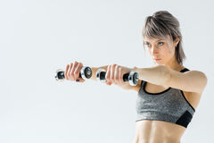 Young sportswoman training with dumbbells on grey Stock Photo