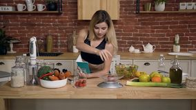 Young sportswoman is weighting cherry tomatoes for prepare healthy food and recording recipe in a notebook at kitchen. Healthy lifestyle, diet, slow motion stock video footage