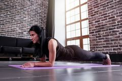 Young sportswoman working-out at home doing plank exercise on yoga mat.  Stock Images