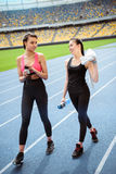 Young sportswomen with bottles of water walking on running track stadium Royalty Free Stock Images