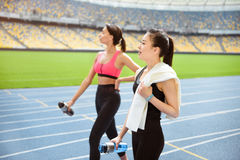 Young sportswomen with bottles of water walking on running track stadium Stock Photo