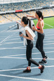Young sportswomen with bottles of water walking on running track stadium Royalty Free Stock Image