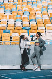 Young sportswomen drinking water near stadium seats Stock Images