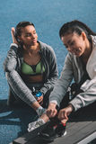 Young sportswomen resting together on running track stadium Royalty Free Stock Images