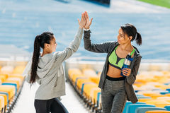 Young sportswomen with sport bottle giving highfive on stadium stairs Royalty Free Stock Photography
