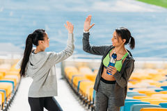 Young sportswomen with sport bottle giving highfive on stadium stairs Royalty Free Stock Image