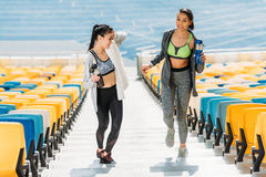 Young sportswomen with sport bottles on stadium stairs Stock Photo