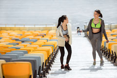 Young sportswomen with sport bottles on stadium stairs Royalty Free Stock Photography