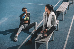 Young sportswomen with sports bottles resting on running track stadium Royalty Free Stock Photography