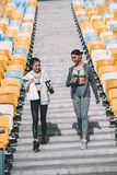 Young sportswomen with sports bottles walking between stadium seats Stock Photos