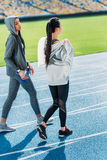 Young sportswomen walking together on running track stadium Stock Images