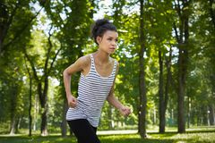 Young woman running in green park, copy space Royalty Free Stock Images