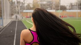 Young sporty asian girl walks at stadium after training and lets her hair down. Young sporty girl pleased with herself walks at stadium after training and lets stock footage
