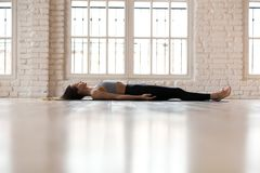 Young sporty attractive woman practicing yoga, Corpse pose. Young sporty attractive woman practicing yoga, doing Dead Body, Savasana exercise, Corpse pose stock image