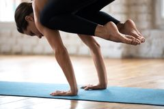Young sporty attractive woman practicing yoga, Crane exercise cl. Young sporty attractive woman practicing yoga, doing Crane exercise, Bakasana pose, working out stock photos