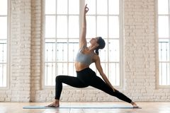 Young sporty attractive woman practicing yoga, doing Reverse War royalty free stock image