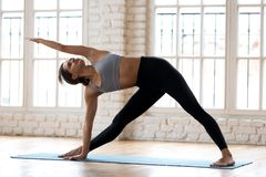 Young sporty attractive woman practicing yoga, doing Utthita Tri stock images
