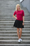 Young sporty beautiful blonde woman standing on the concrete stairs and looking into camera Stock Image