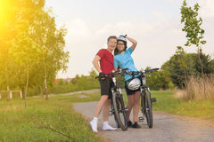 Young Sporty Biker Couple in Sunny Day Outdoors. Happy Sporty Biker Couple in Sunny Day Outdoors. Horizontal Composition Royalty Free Stock Images