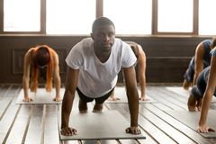 Young sporty black man in Plank pose. Portrait of young happy black men and a group of sporty people practicing yoga lesson standing in Plank pose, doing Push royalty free stock images