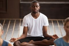 Young sporty black man sitting in Sukhasana exercise. Young sporty black men practicing yoga lesson, sitting in Sukhasana exercise, Easy Seat pose with mudra Stock Photography