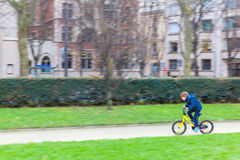 Young sporty boy rides a bicycle on Paris street Royalty Free Stock Photos