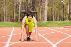 Young sporty boy in start position at racetrack. Young athlete, teenage boy kneeling in start position at racetrack with hands on the line Stock Photo