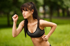 Young sporty brunette woman in sportswear jogging in park Stock Image