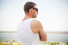 Young sporty Caucasian man in white shirt, back. Young sporty Caucasian man in white shirt and sunglasses starring at the sea in bright summer day Stock Images