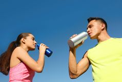 Young sporty couple drinking from water bottles against blue sky. On sunny day royalty free stock images