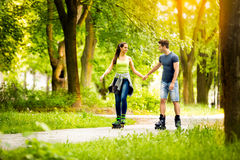 Young sporty couple ride rollerblades Royalty Free Stock Photography