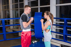 Young sporty couple in sportswear training in regular boxing rin Royalty Free Stock Photography