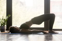Young sporty doing pilates or yoga Glute Bridge pose royalty free stock photography