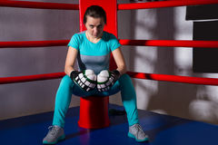 Young sporty female boxer in boxing gloves sitting near red corn stock image