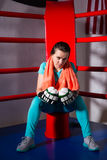 Young sporty female boxer with a towel around her neck sitting i Royalty Free Stock Image