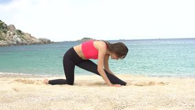 Young sporty female does stretching exercise on the beach near the sea. Healthy active lifestyle concept. stock video footage